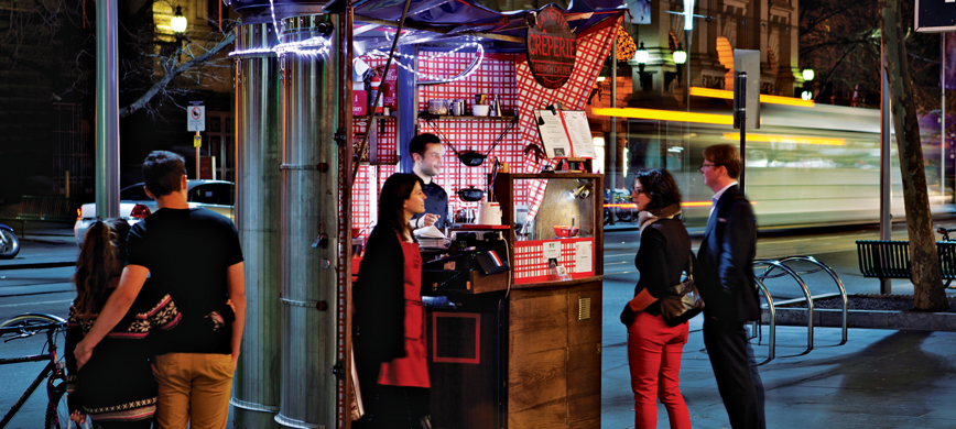 Customers stand around a tiny creperie, housed in an old newspaper cylinder