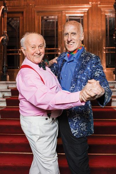Two older men dance together