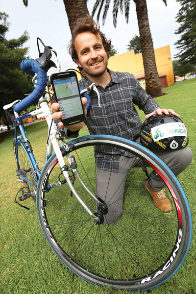 A man with a bike holds up his mobile phone.