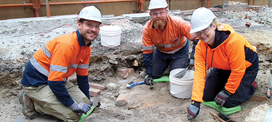 Three archaeologists at work in a trench