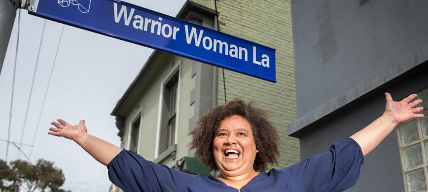 Woman with arms outstretched under street sign