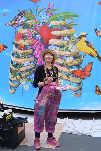 An artist in front of a colourful mural