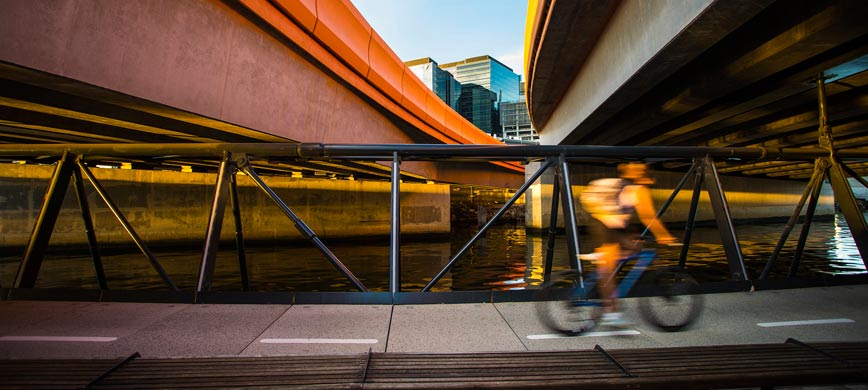 A cyclist passing under a bridge, by a river
