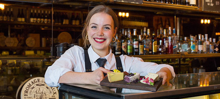 A hospitality worker presents a cheeseboard