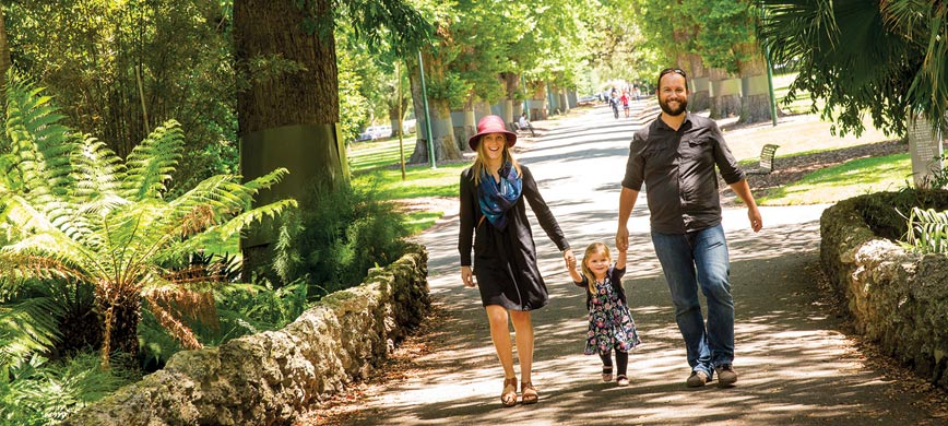 Two adults and a child walking through a park