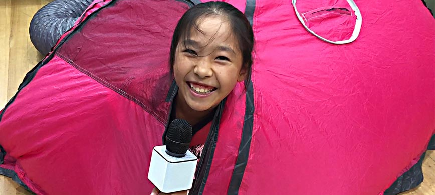A smiling child holding a microphone peeks out of a bright inflatable object