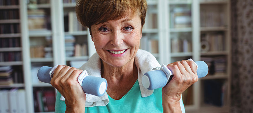 An older person exercising indoors, holding hand-weights