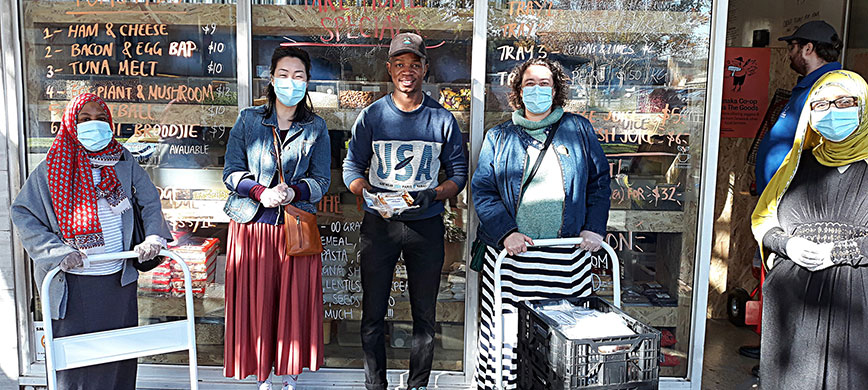 A group of people in face masks outside a cafe, with trolleys of food