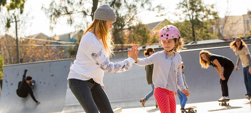 A woman gives a child a high five as they skateboard side-by-side