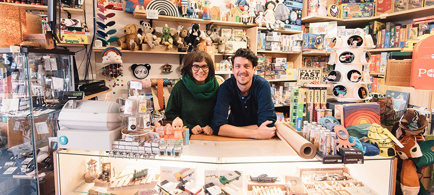 Two people behind the counter of a colourful toy and gift shop