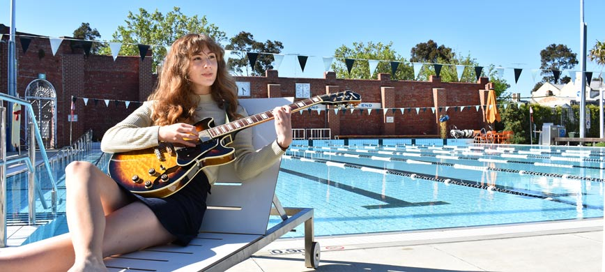 A person playing guitar beside a pool