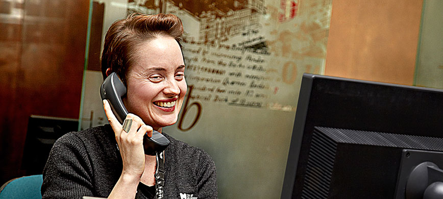 A smiling person on the phone, behind a computer