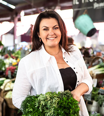 A person, in front of a fruit and vegetable stall, holding some greens