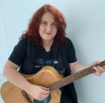 A person with red hair and a guitar