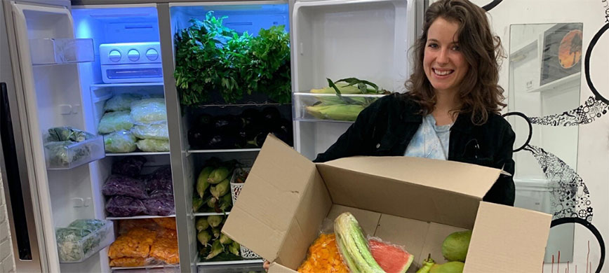 A person holding a box of vegetables