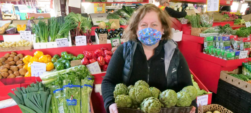 A fruit and veg stall owner wearing a mask, holding a basket of artichokes