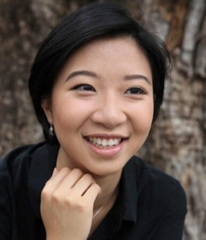 A woman with short black hair, smiling