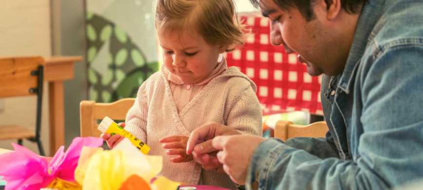 A parent and child doing craft