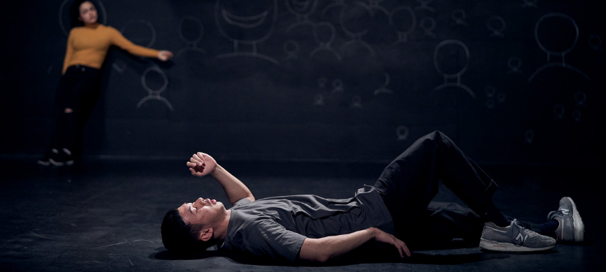 A young person lying on the floor in a dark space, a person in a yellow shirt looks on