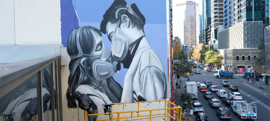 An artist working on a mural high above a city street - the mural shows two people wearing masks and hugging