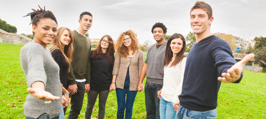 A group of young people standing in a semi-circle in a park