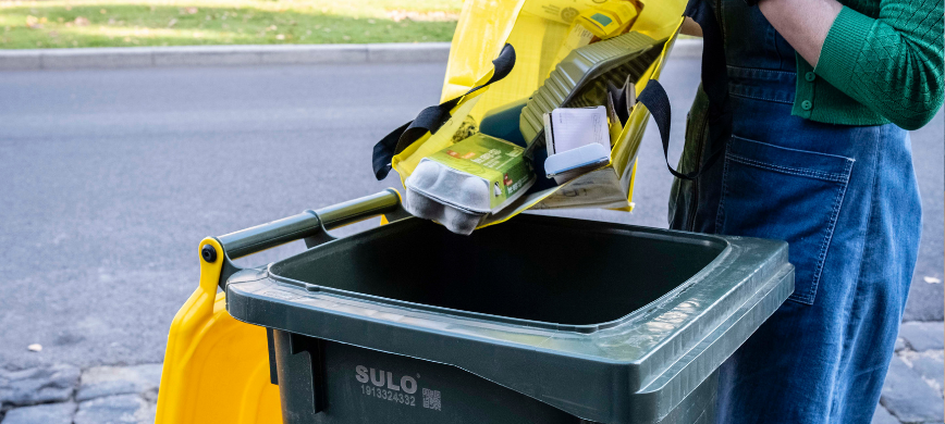 Recyclables being tipped into a yellow-lid bin