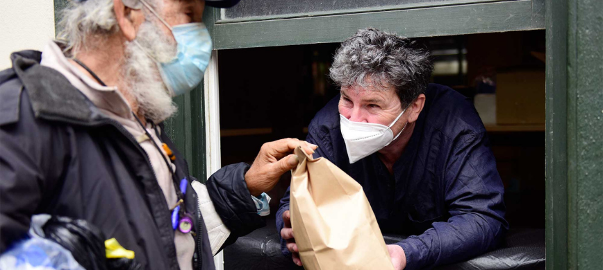 A person passing a brown paper food bag to another person, both are wearing face masks