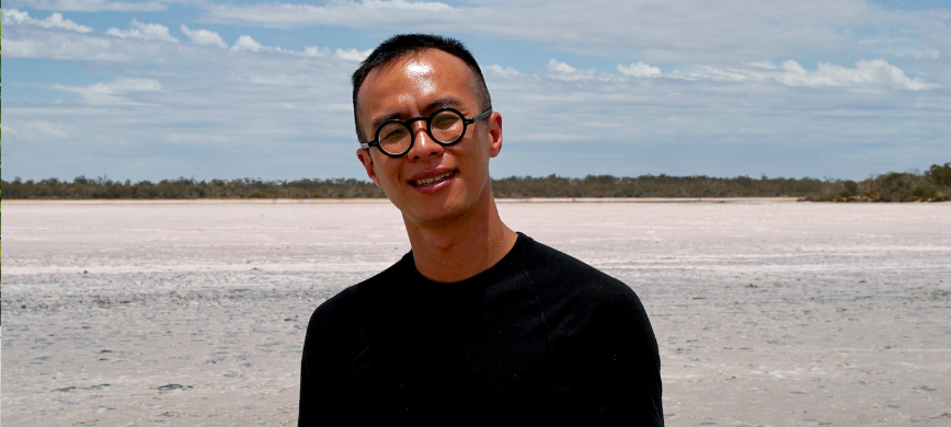 A person with an inland pink lake behind them smiling with round black glasses and short black hair