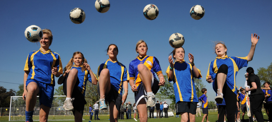 A row of young people kicking soccer balls into the air