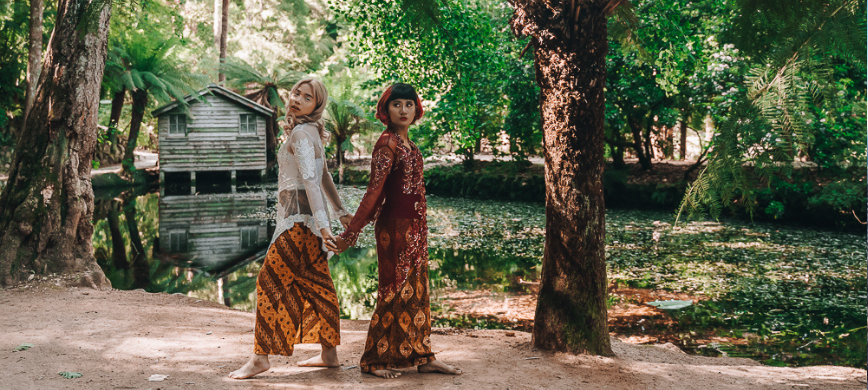 Two young people in Indonesian dress stand in a forest