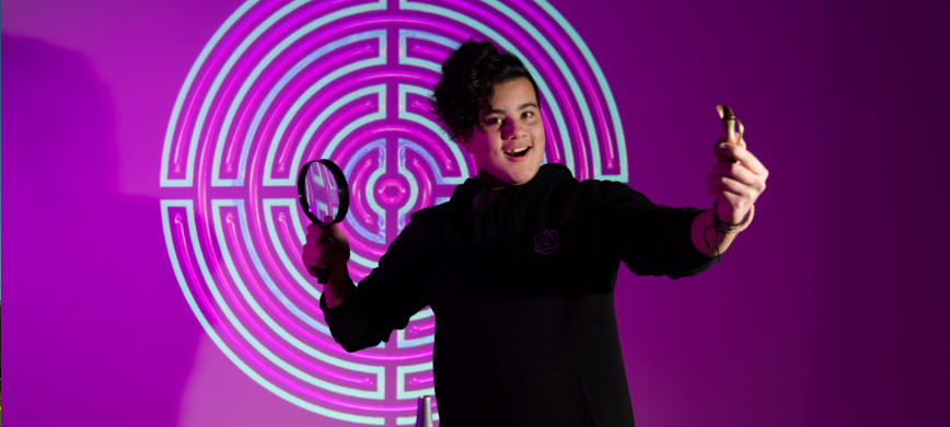 A young person with a magnifying glass posing in front of a vibrant purple background