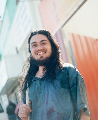 A person with long hair standing in front of a colourful backdrop and smiling