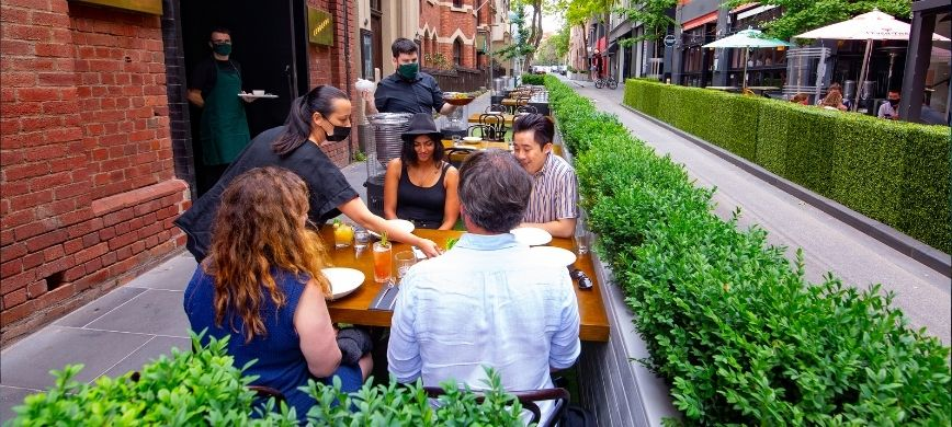 A group of people dining on a city pavement