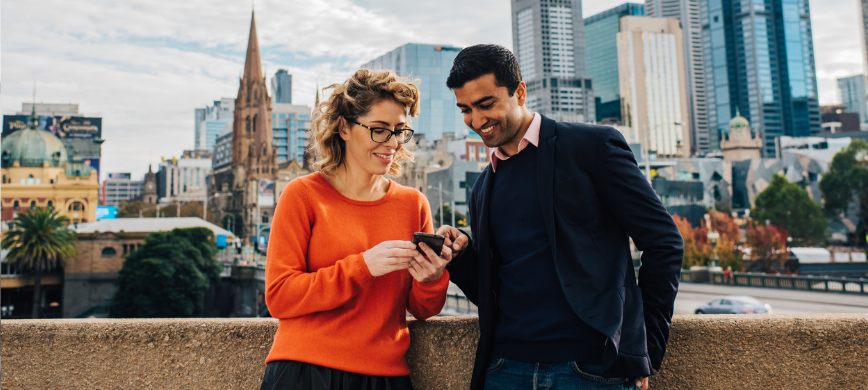 Two people look at a smartphone in front of the Melbourne city skyline