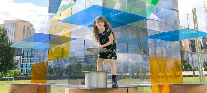 A child putting a metal lid on a large container in front of a colourful background
