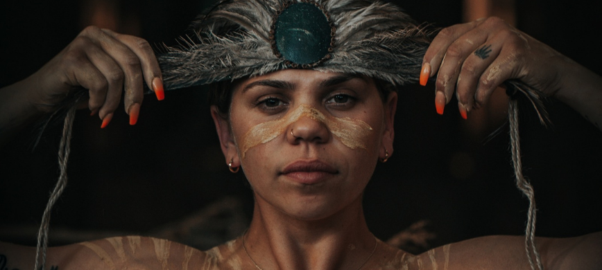 An Aboriginal woman with orange nail polish tying a feathered band around her head