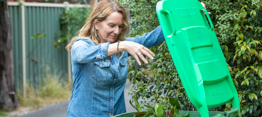 A person throwing leaves into a wheelie bin with a green lid