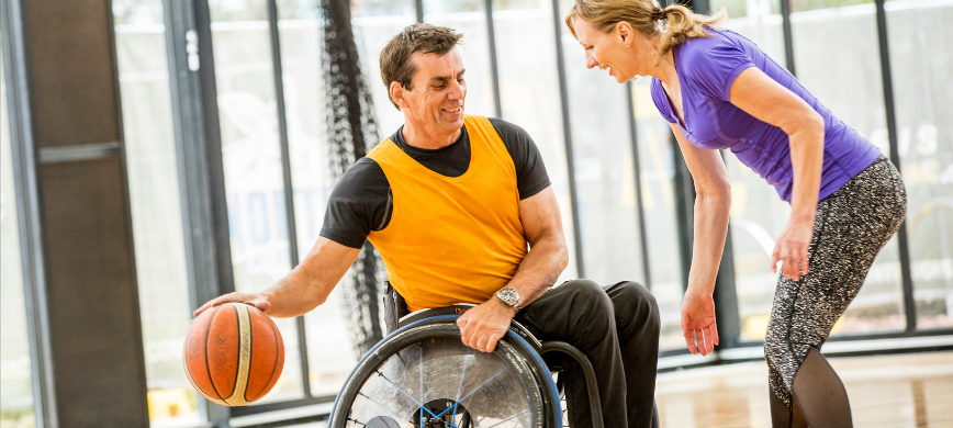 Two people playing basketball, one is using a wheelchair