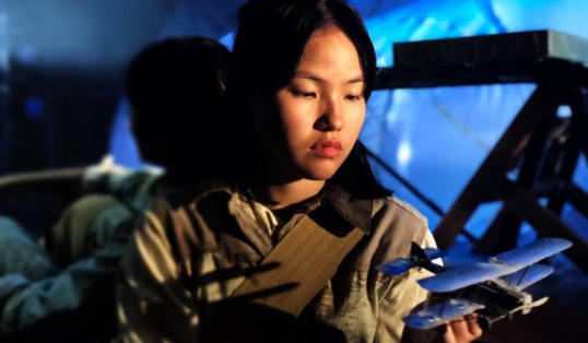 A young person in a dimly lit space holding a small model bi-plane