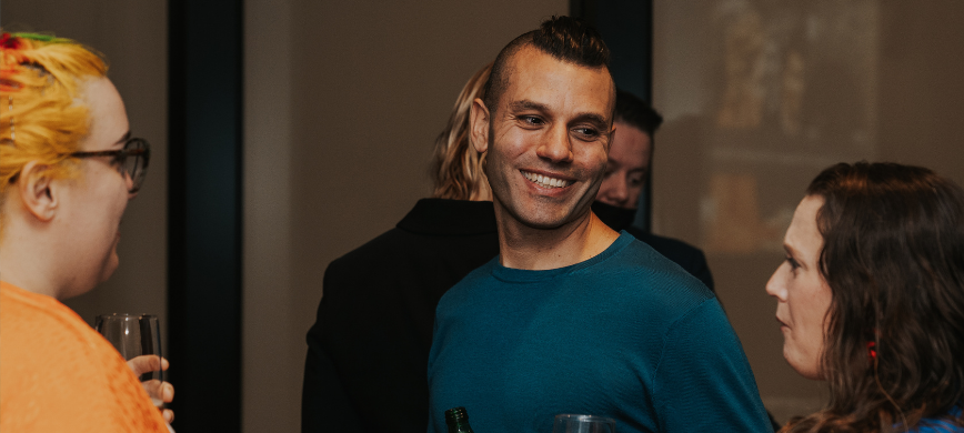 A person in a dark teal top smiling and chatting to others at an event