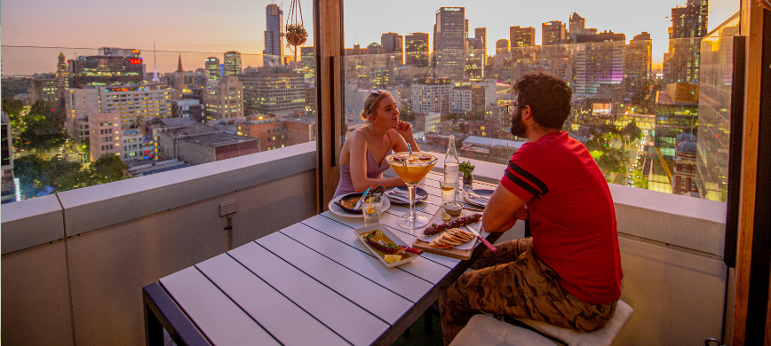 Two people dining at a rooftop restaurants