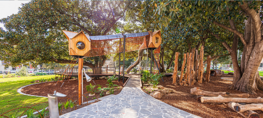 A playground with a high pathway through the trees
